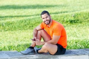 Cheerful muscled guy smiling at camera on stroll and sitting on concrete slab. Happy modern sportsman with smartphone spending time in park after training. Technology and sport concept