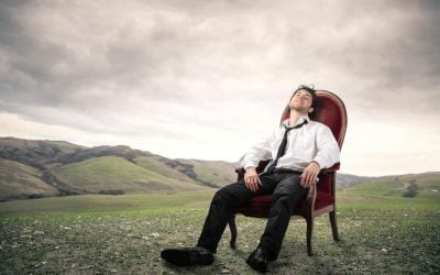 Man resting in chair in a field with mountains in the background
